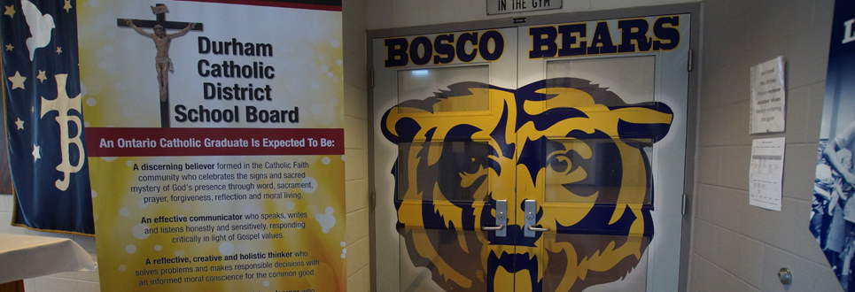 Stand-up sign of Catholic Graduate Expectations beside double doors painted with a giant grizzly bear face with BOSCO BEARS painted above it.