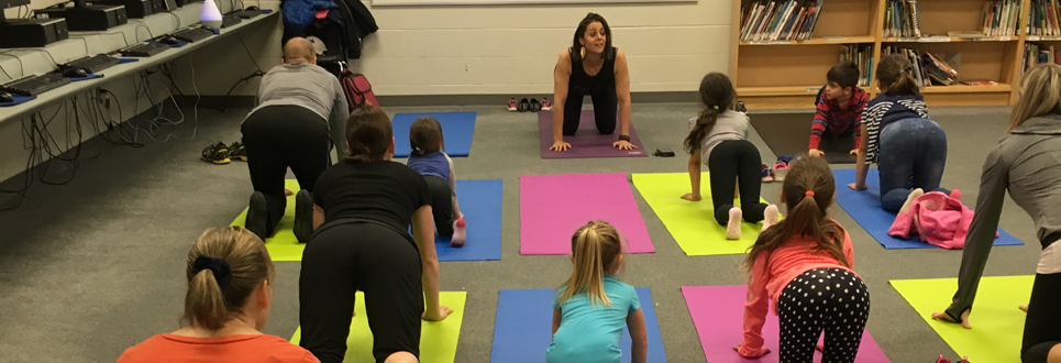 A dozen students practicing yoga, an instructor at the front of the room.