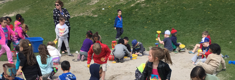A class of younger students playing in the sand and grass.